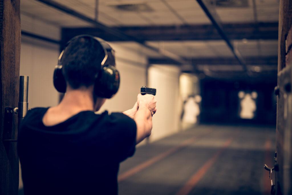 Mężczyzna w słuchawkach zabezpieczających celuje z broni krótkiej na strzelnicy. W oddali widać rozmyty cel.