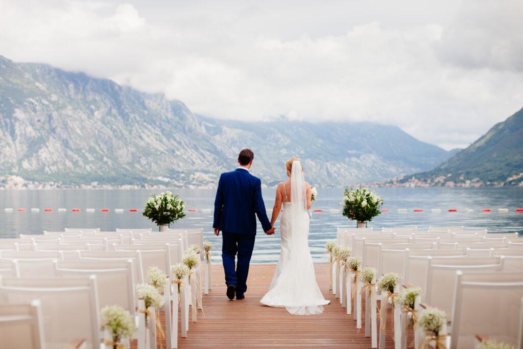 Para młoda idąca wśród udekorowanych miejsc dla gości, na pomoście z pięknym widokiem