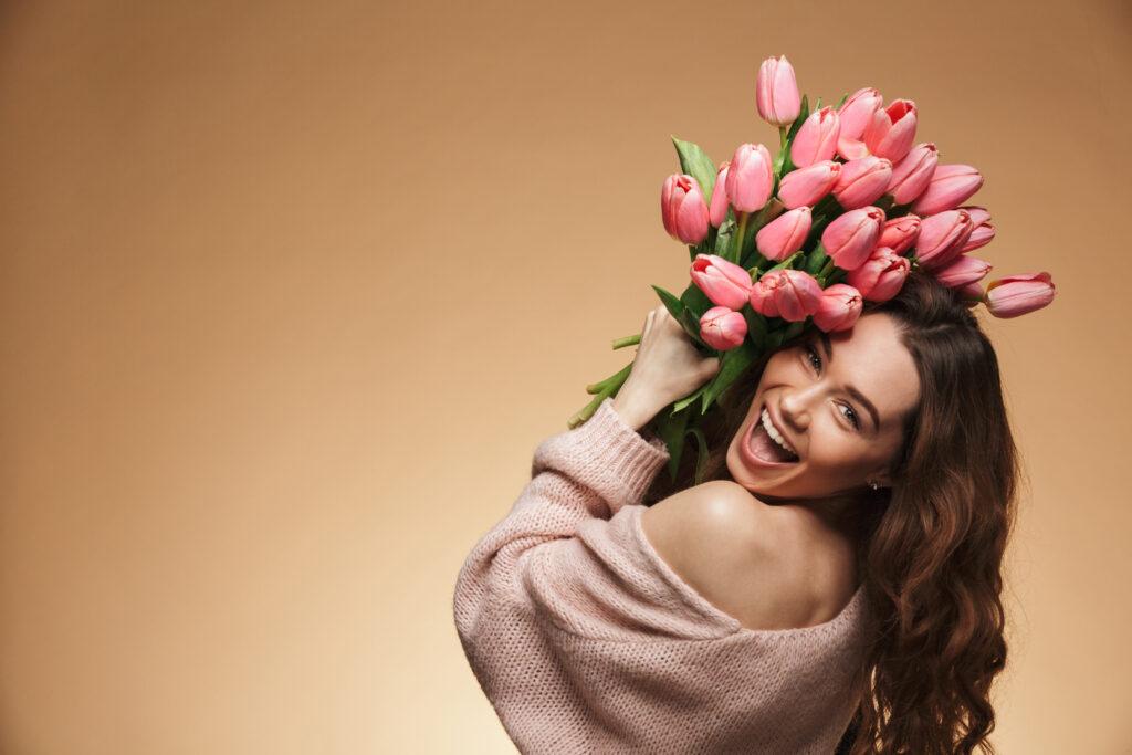 Uśmiechnięta kobieta unosi bukiet różowych tulipanów.