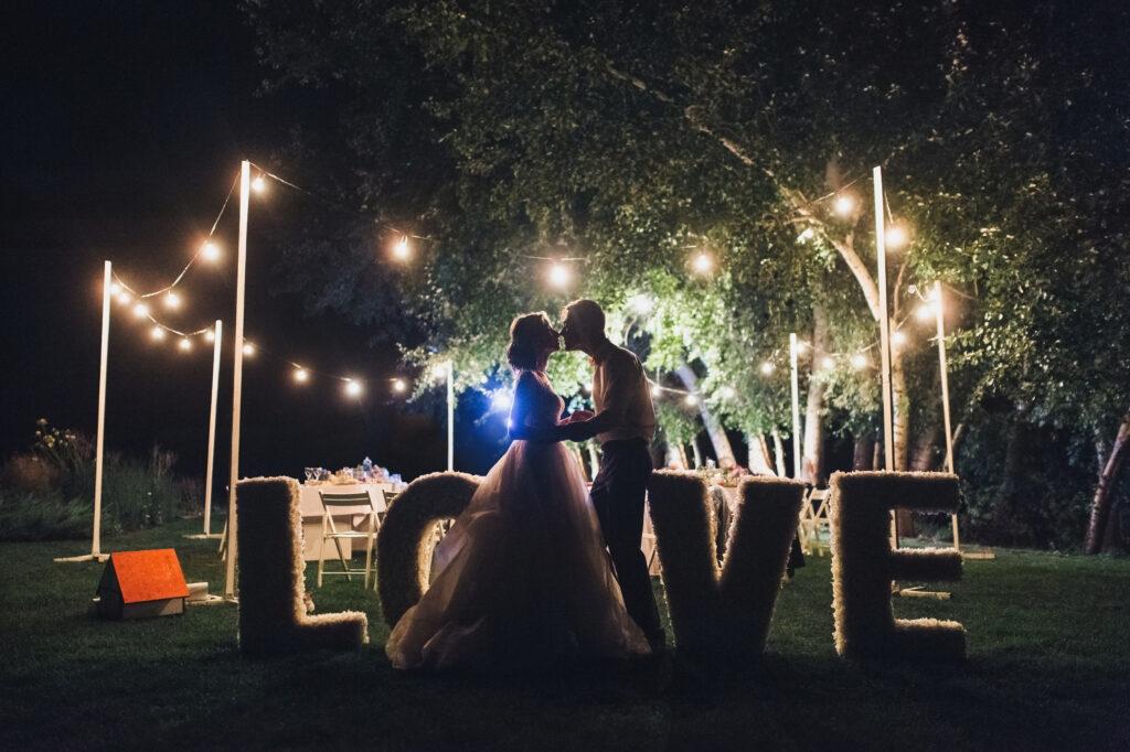 Całująca się młoda para po zmroku na tle napisu love.