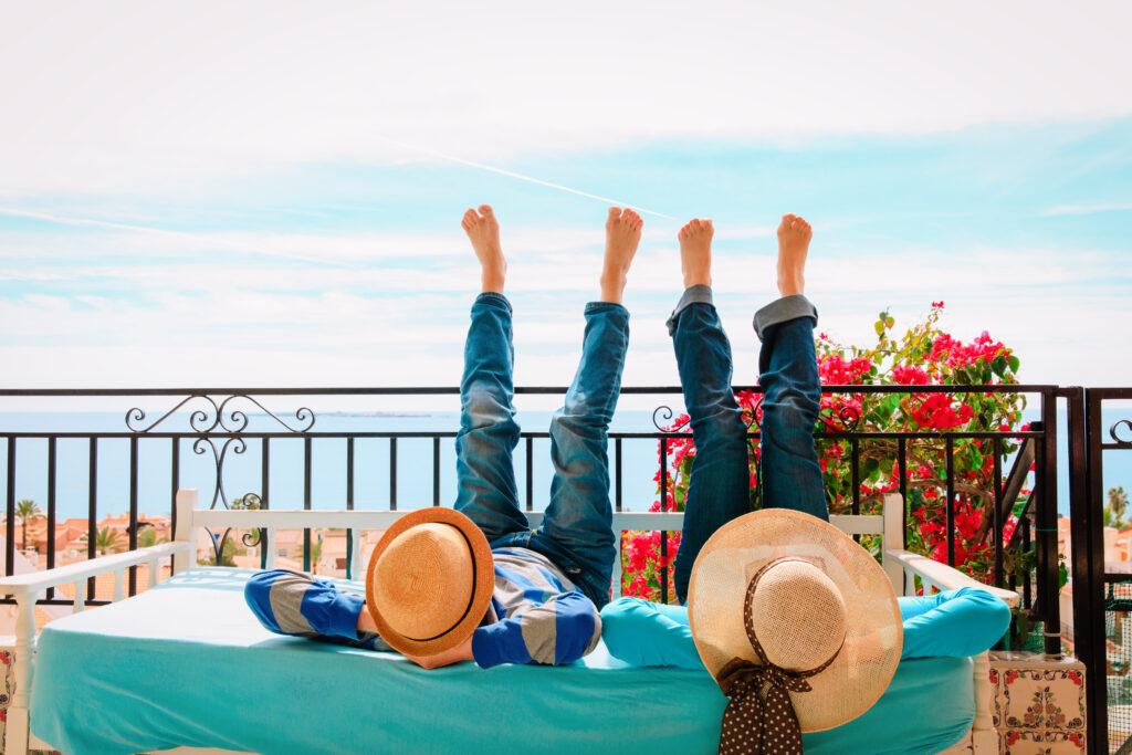 Dwie osoby na tarasie z widokiem na morze. Leżą kopytkami do góry.