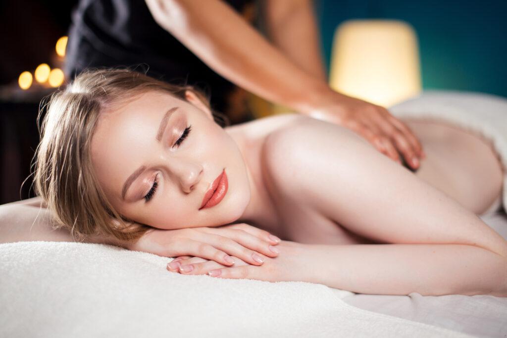 Zrelaksowana kobieta leży podczas masażu pleców w spa.