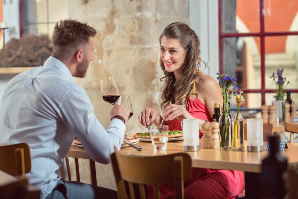 Mężczyzna pije wino patrząc na kobietę jedzącą pizze