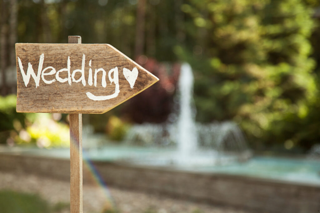 Na zdjęciu drewnany drogowskaz z napisem wedding.