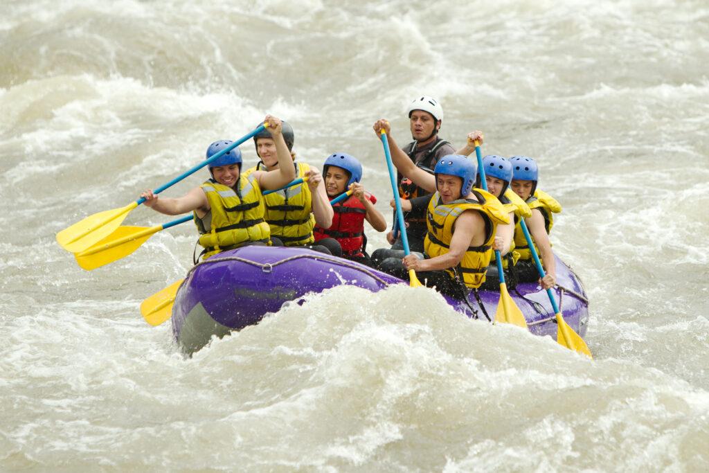 Grupa ludzi w kapokach podczas spływu kajakowego.