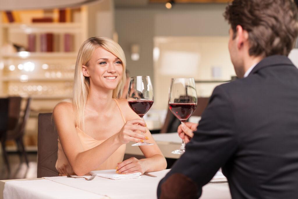 Para siedząc w restauracji przy stoliku wznosi toast czerwonym winem.