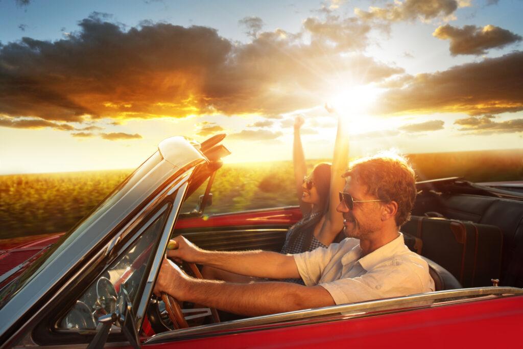 Para jadąca samochodem, podczas zachodu słońca.