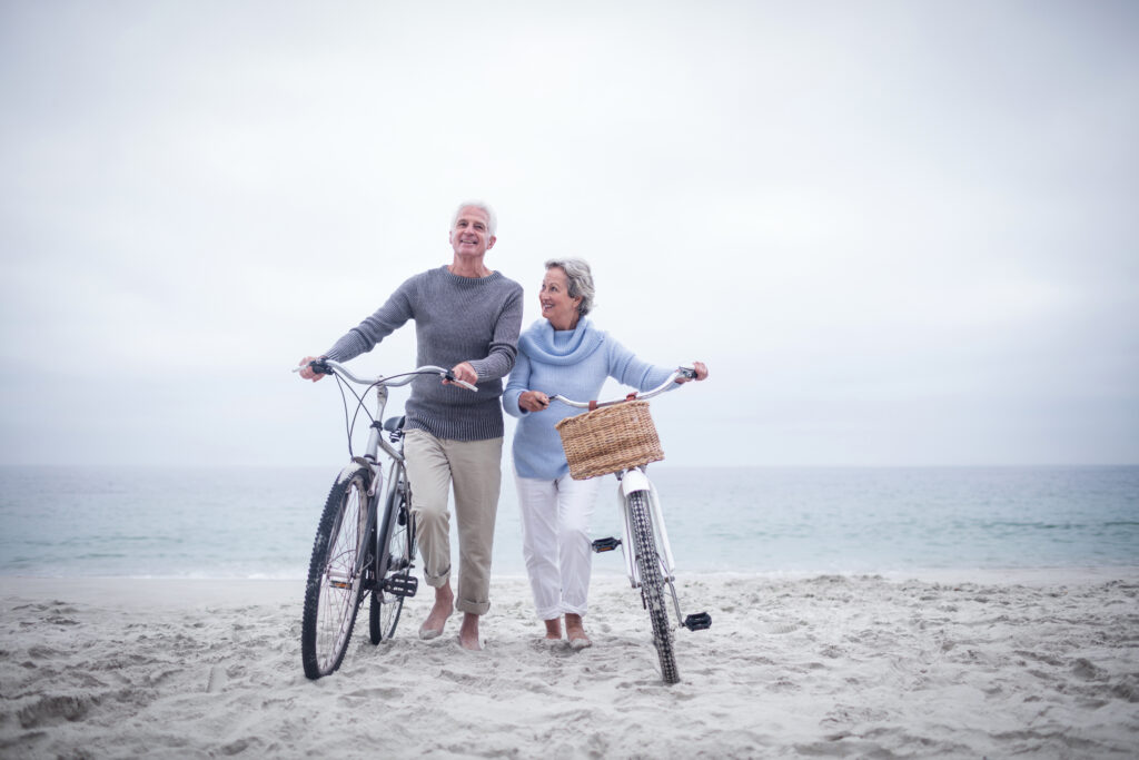 Para prowadzi rowery po plaży, uśmiechając się. W tle spokojne morze.