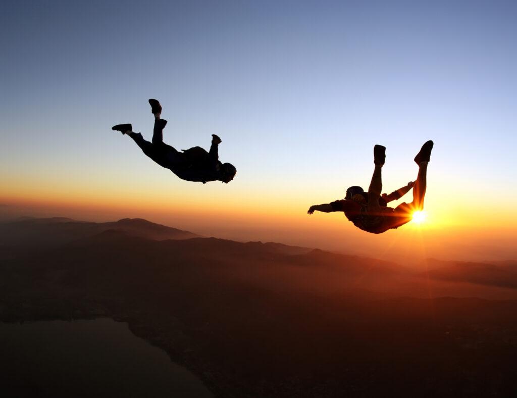 Dwie osoby szybujące , podczas skoku ze spadochronem na tle zachodzącego  słońca.