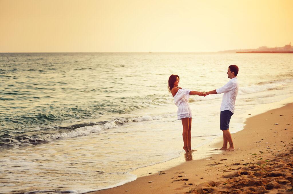 Trzymająca się za ręce para na plaż podczas zachodu słońca.