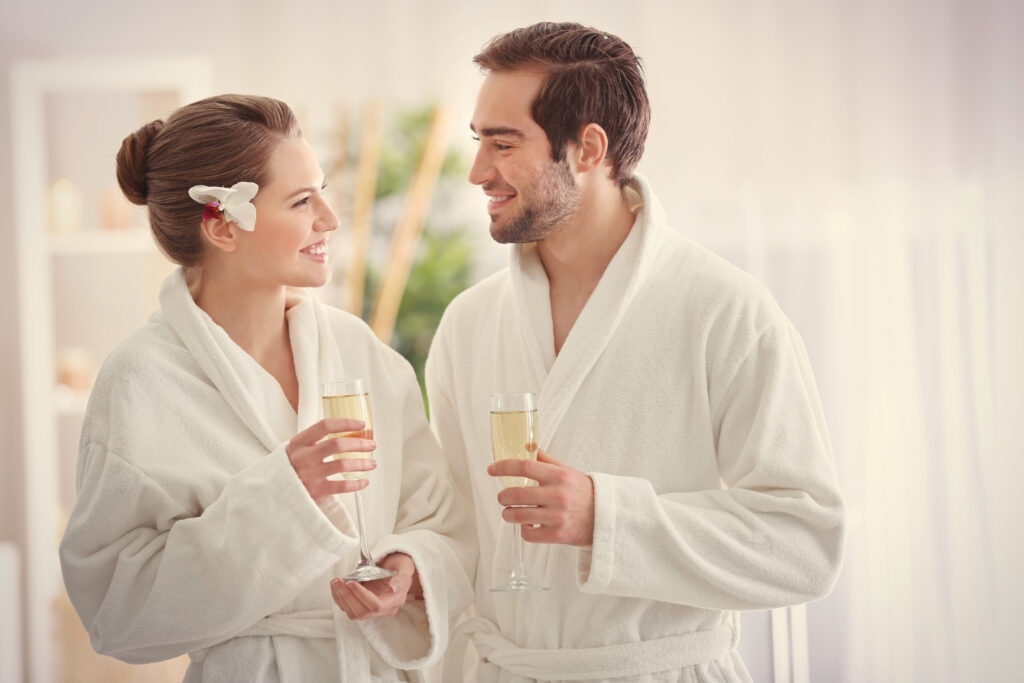 Uśmiechnięta para, pije wino w białych szlafrokach, patrząc na siebie.