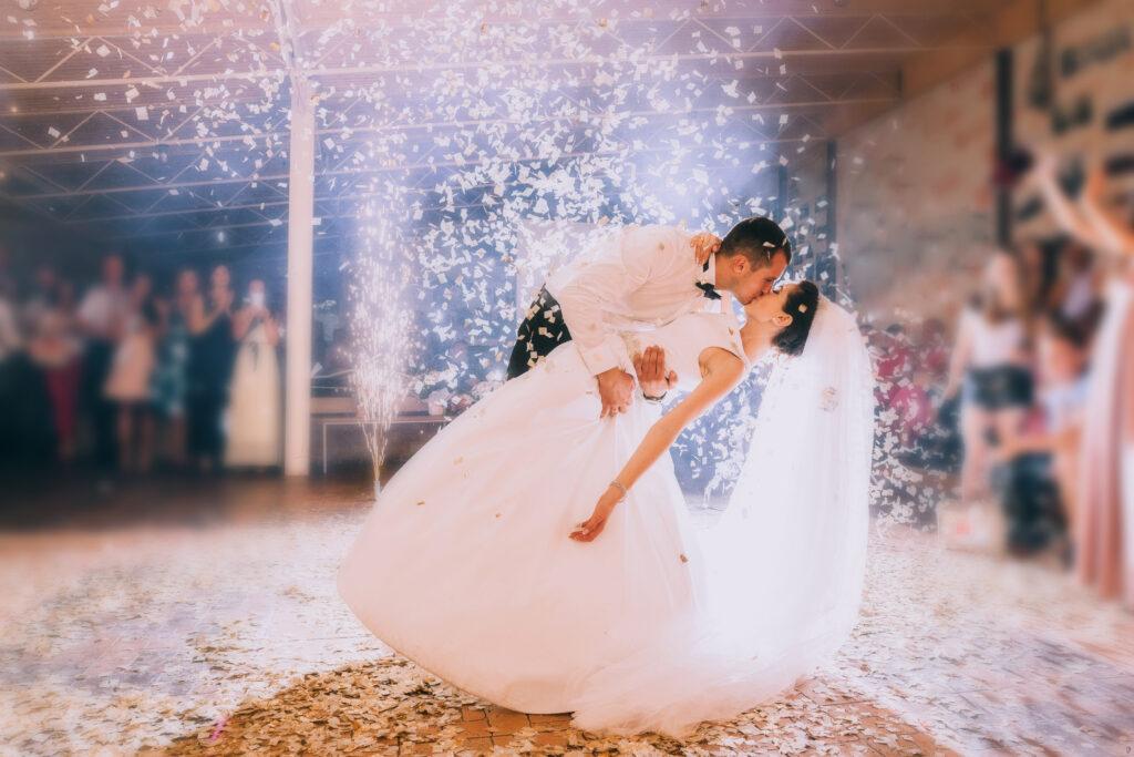 Młoda para, obsypana białym konfetti całuję się podczas pierwszego tańca na weselu. W tle goście weselni.