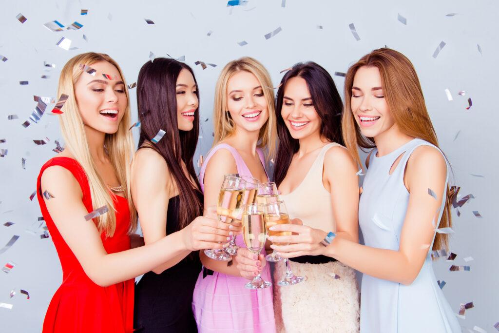 Uśmiechnięte kobiety wznoszą toast, obsypane konfetti.