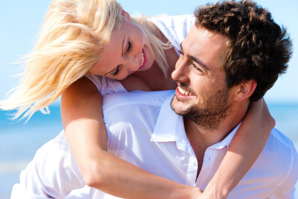 Kobieta obejmuje roześmianego mężczyznę w białej koszuli patrząc mu w oczy.