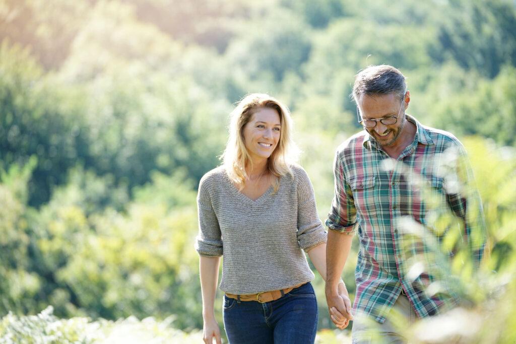 Uśmiechnięta kobieta spaceruje za rękę z mężczyzną, w tle rozmyte drzewa i krzewy.