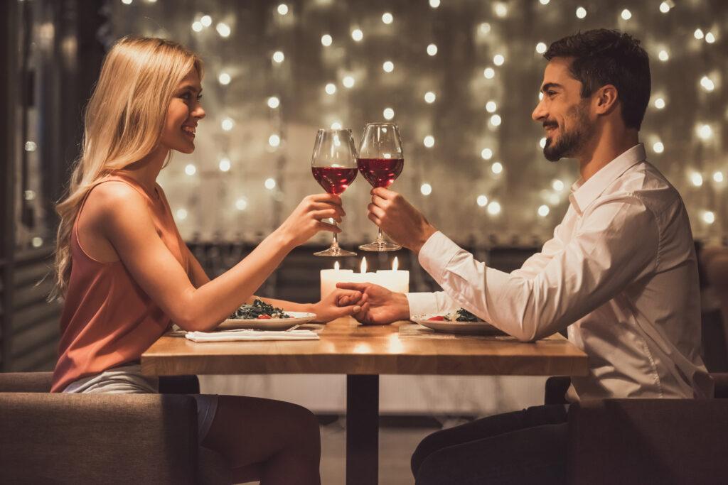 Para wznosząca toast czerwonym winem przy stoliku, rozświetlonym świecami.