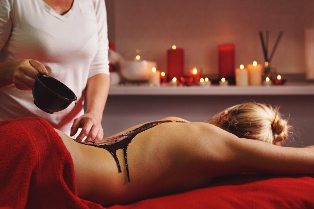 Zrelaksowana kobieta podczas masażu czekoladą