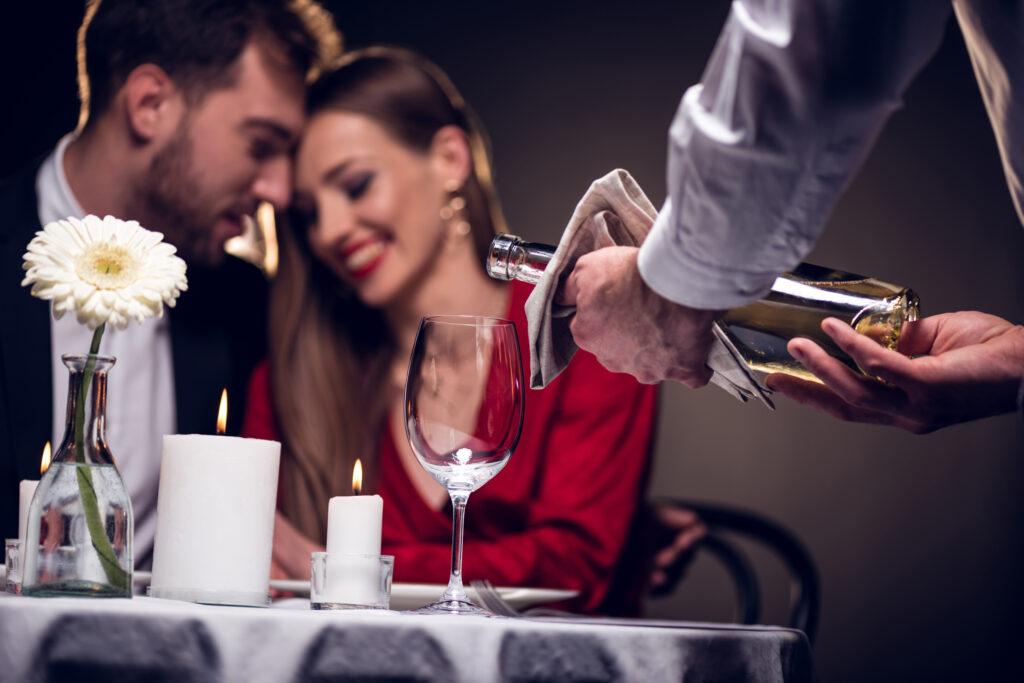 Kelner nalewa wino do lampki, stojącej na stoliku. W tle przytulona uśmiechnięta para.