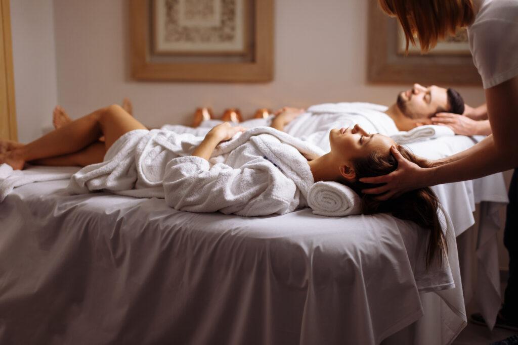 Para w białych szlafrokach leży podczas masażu głowy na łóżkach w spa.