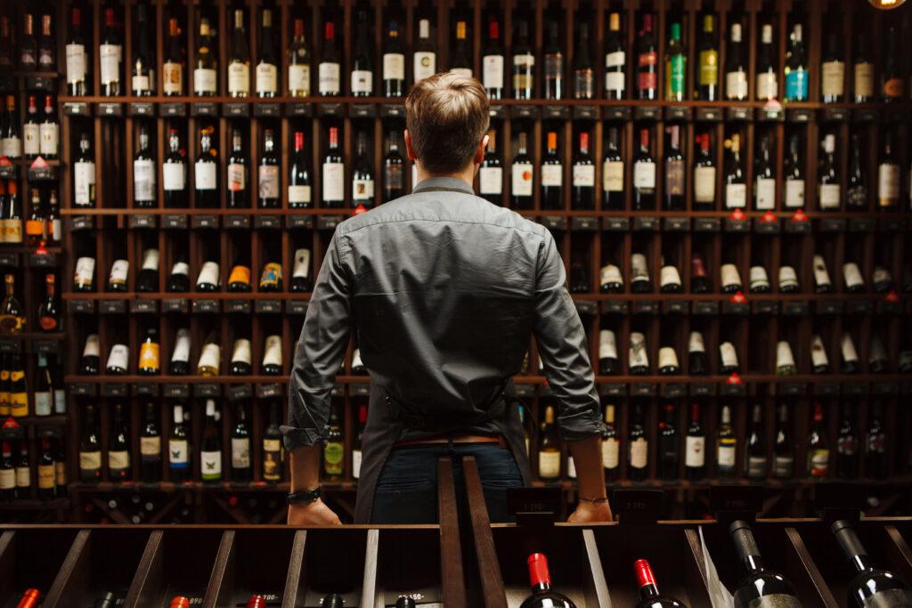 Mężczyzna stojący na tle półek z winem.