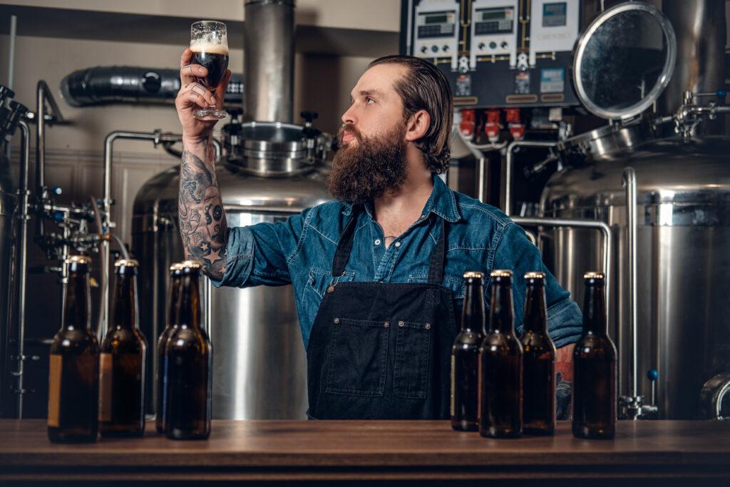 Mężczyzna z kuflem ciemnego piwa na piwowarni.