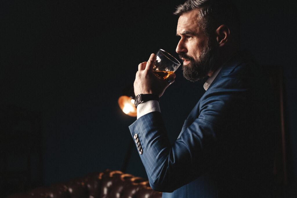 Mężczyzna w garniturze degustuje whisky.