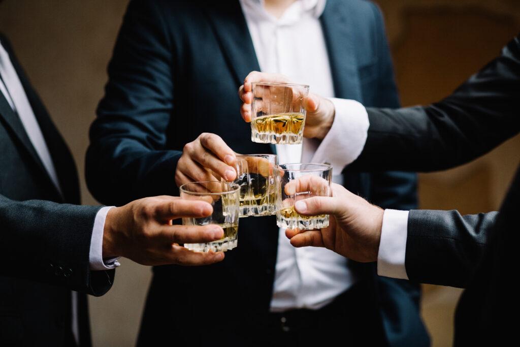 Degustacja whisky- wznoszenie toastu przez eleganckich mężczyzn.