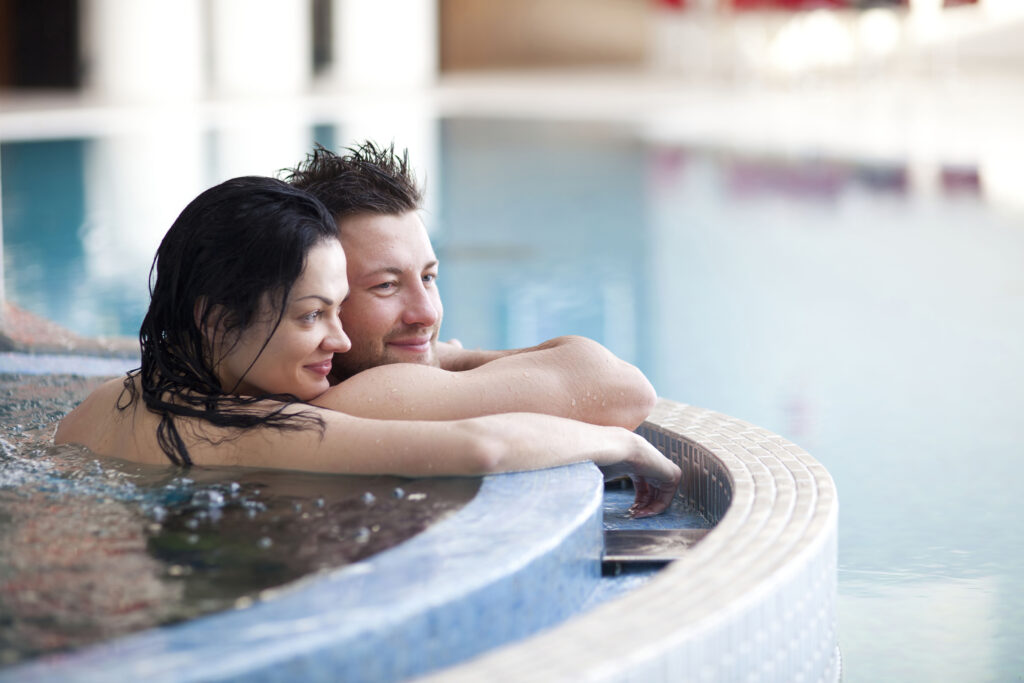 Uśmiechnięta para odpoczywająca w jacuzzi.