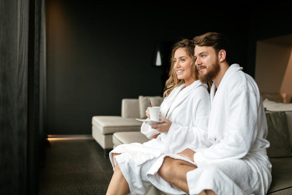 Przytulona para w białych szlafrokach, siedzi sobie z filiżanką.
