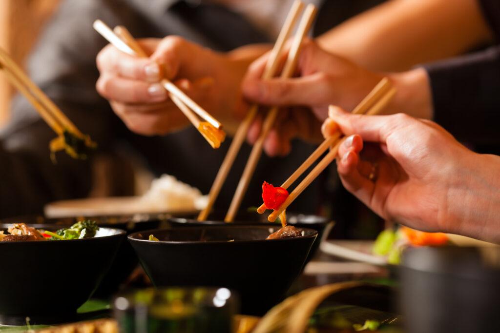 Kilka rąk posługujących się pałeczkami do jedzenia.