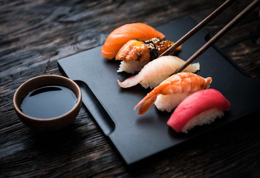 Wyeksponowane sushi na ciemnej desce z miseczką sosu sojowego. Po jeden kawałek sięgają dwie pałeczki.