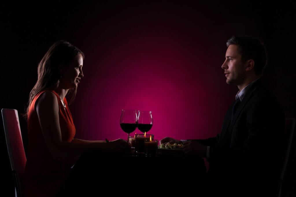 Kobieta i mężczyzna, wino, randka, ciemność.