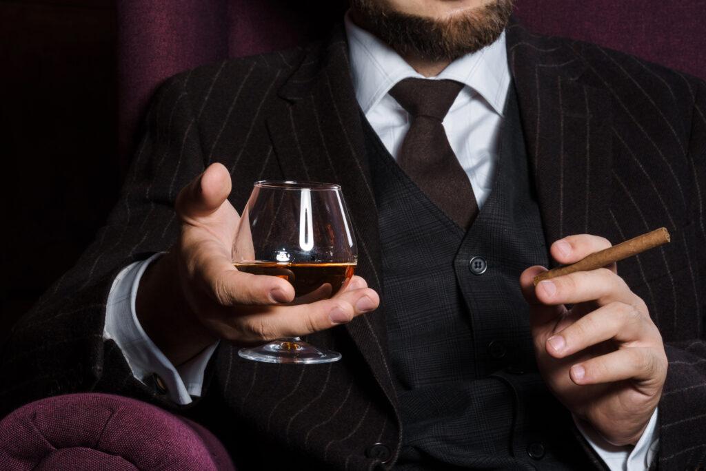 Mężczyzna w garniturze z cygaretką i pełną koniakówką