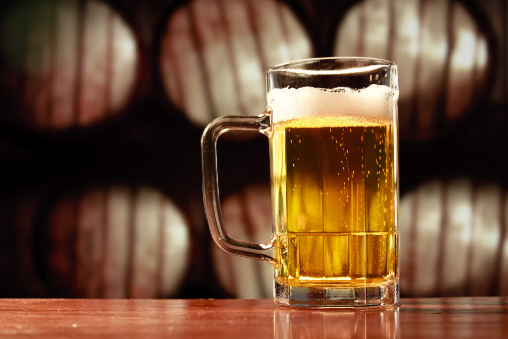 Kufel z piwem jasnym i pianką.