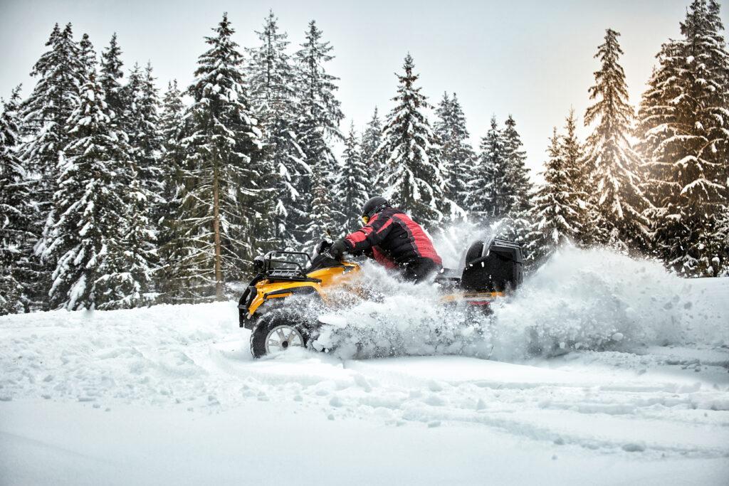Mężczyzna jadące na quadzie w śniegu. W tle ośnieżone choinki.