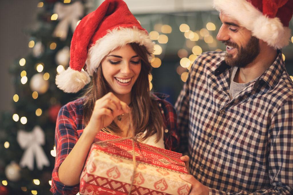 Kobieta otwierająca prezent u boku mężczyzny w świątecznej czapce mikołaja.
