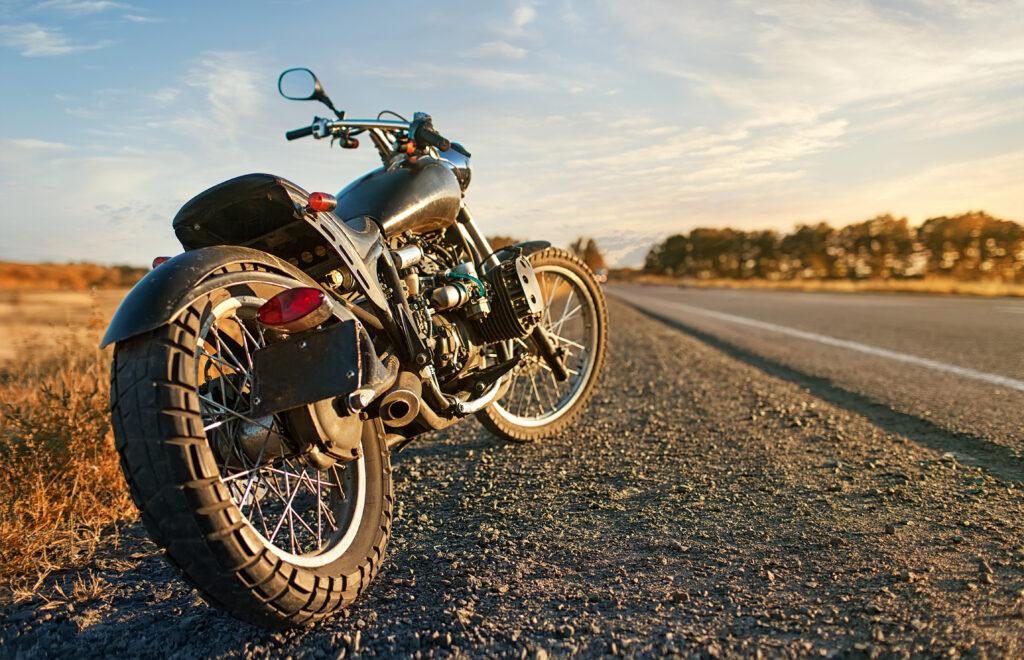 Motocykl, stojący na drodze, w tle jakieś drzewa i pole. Nad nim błękitne niebo.