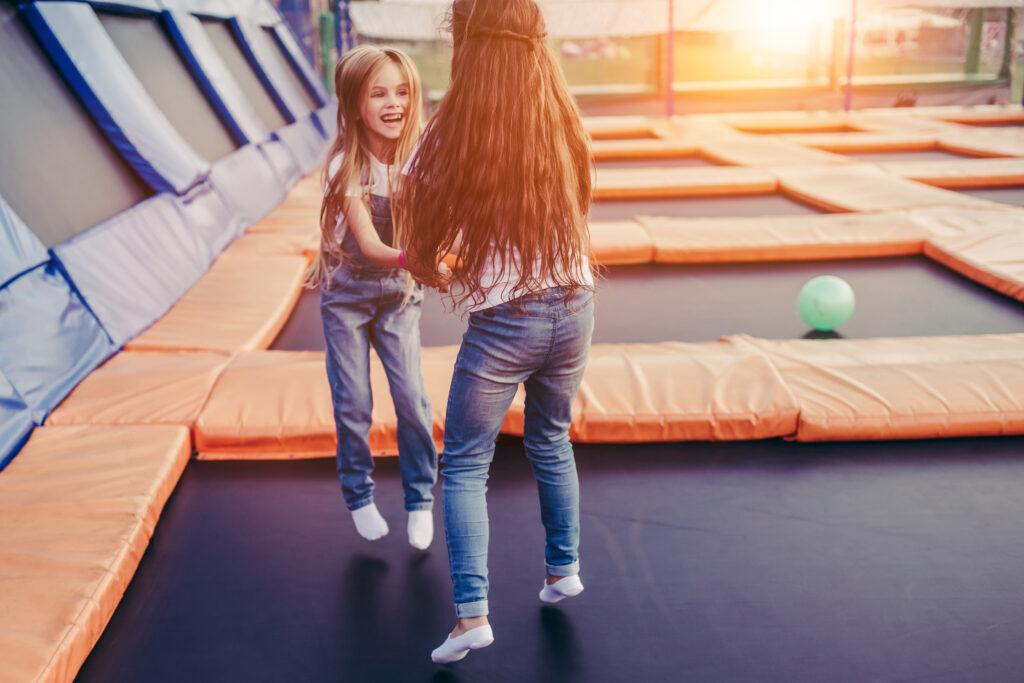 Dwie małe dziewczynki skaczące na trampolinie, park trampolin.