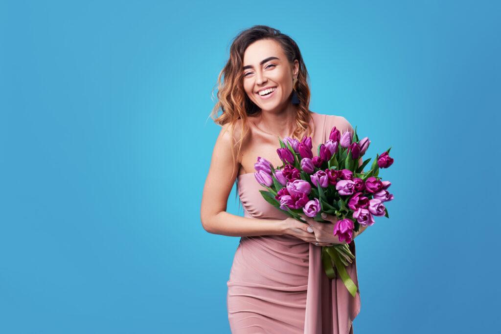kobieta, kwiaty, tulipany, kobieta z kwiatami, niebieskie tło, różowa sukienka, uśmiech, imieniny