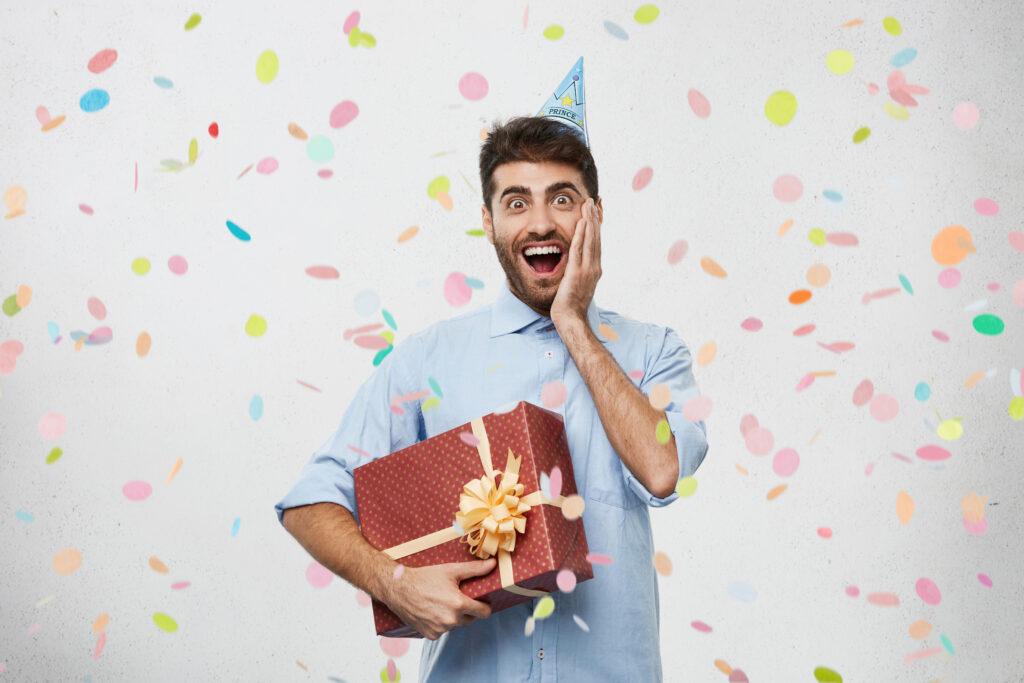 prezent, mężczyzna w czapeczce, zaskoczony, radość