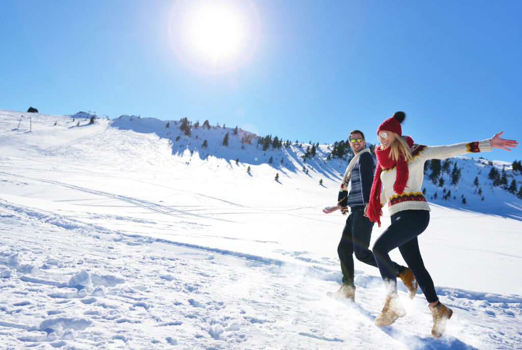 Kobieta i mężczyzna na narciarskim stoku zimą.