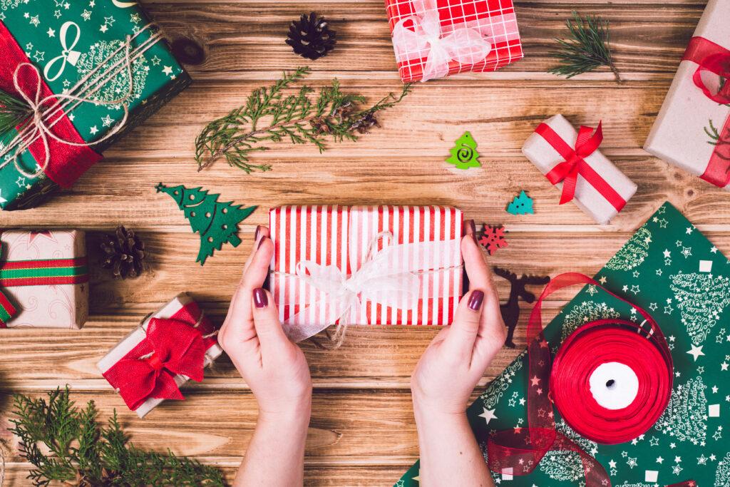 Zapakowany świąteczny prezent w dłoniach kobiety, na stole pełnym dekoracji.