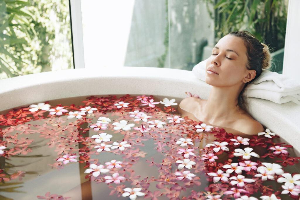Kobieta w wannie z płatkami róż relaksuje się.