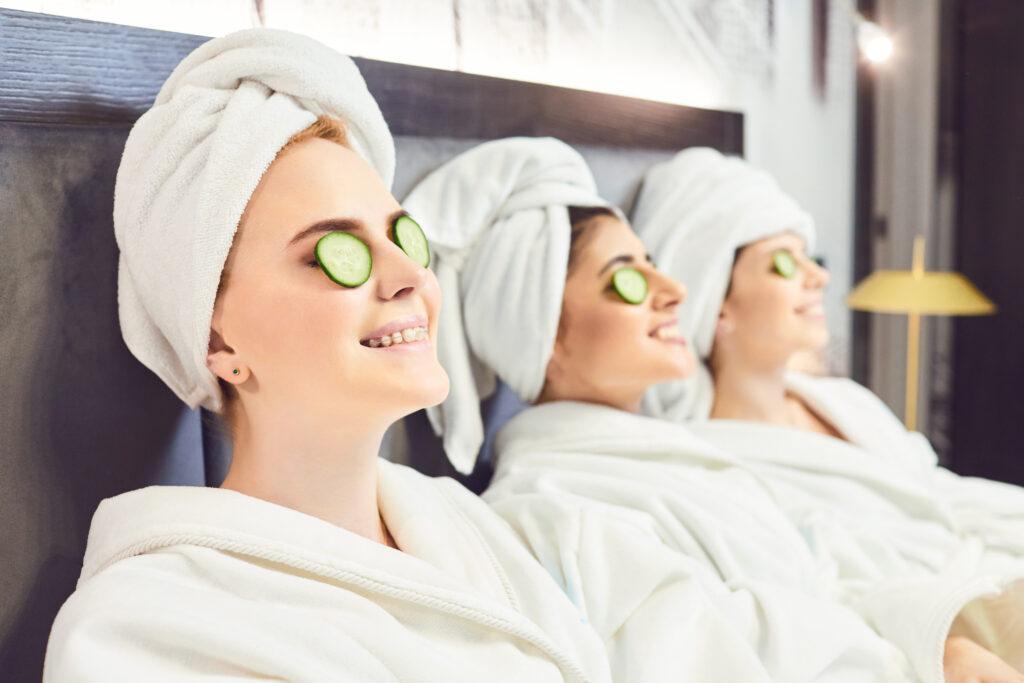 Zrelaksowane trzy młode kobiety w białych szlafrokach i ręcznikach z plastrami ogórków na oczach.