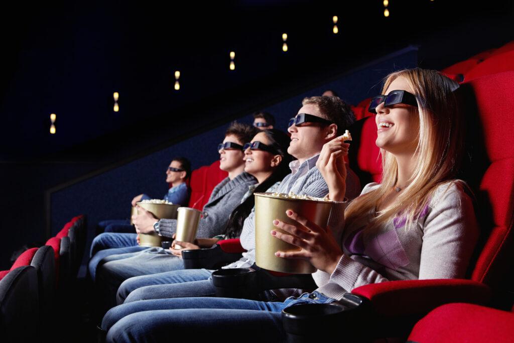 Kinowa sala z wpatrzonymi w ekran osobami w okularach 3D.