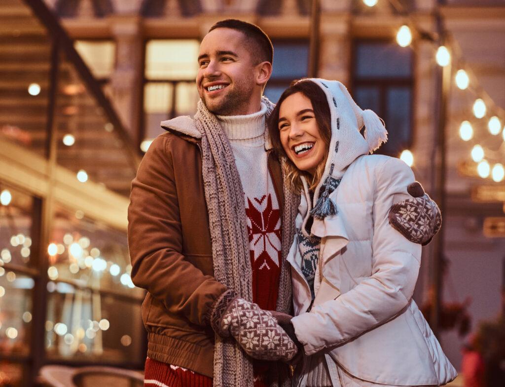 Przytulająca się para w zimowym otoczeniu, lampki światełka czapeczki.