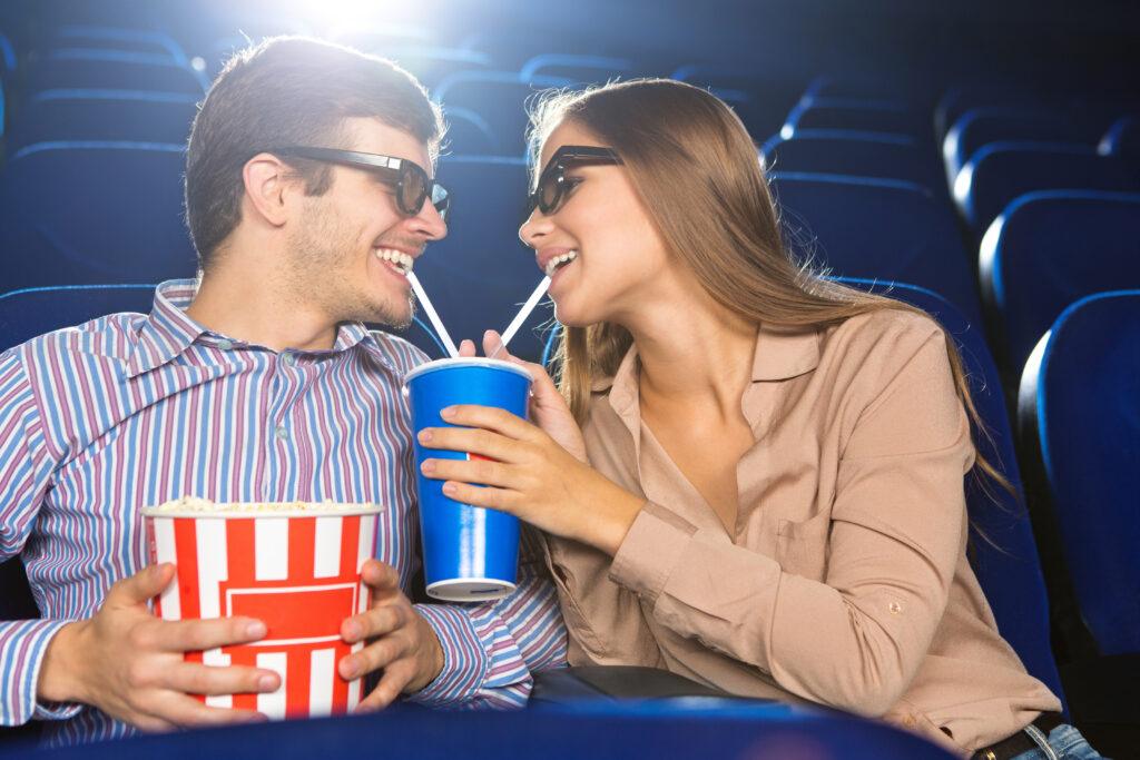 Para w kinie pijąca nadój z jednego kubka, za pomocą dwóch słomek