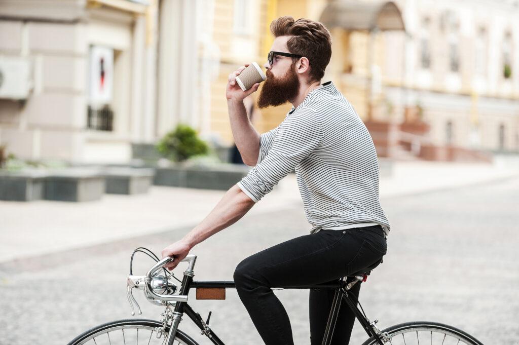 Mężczyzna na rowerze, pijący kawę.