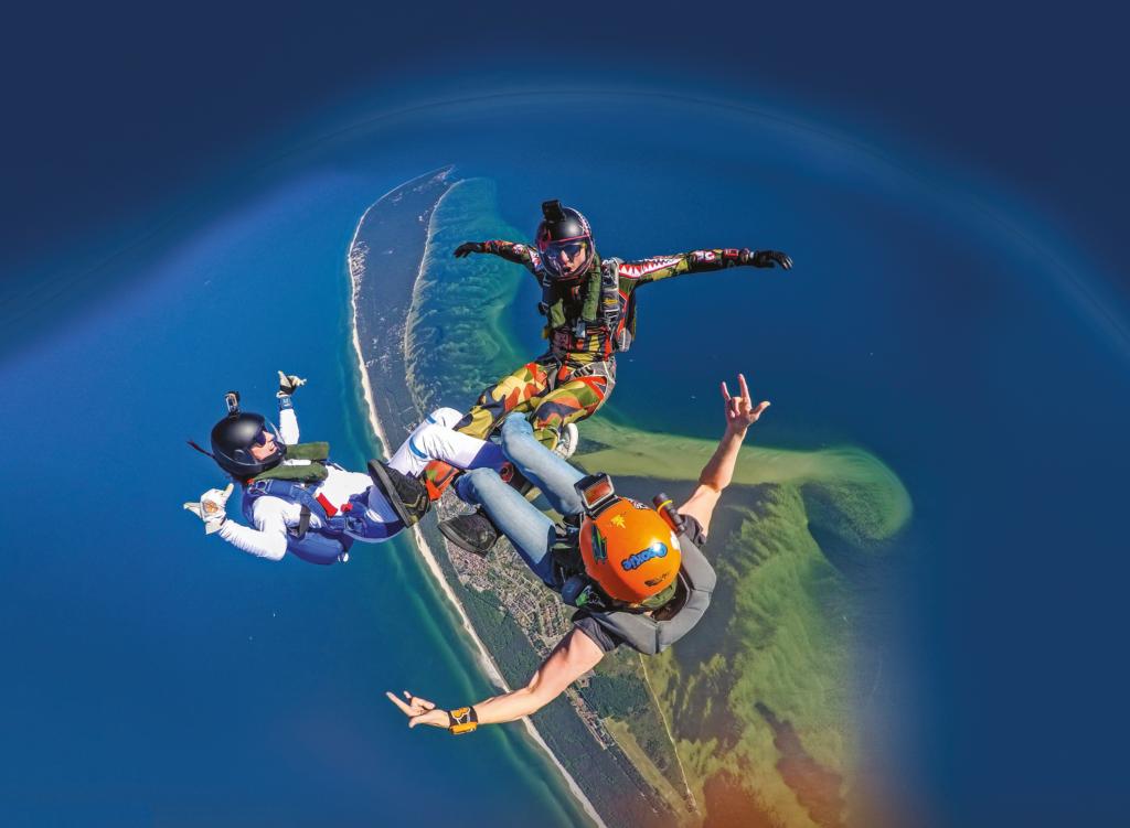 Ludzie skaczący ze spadochronem, właściwie trójka ludzi. Okładka pakietu Polska Pełna Przeżyć