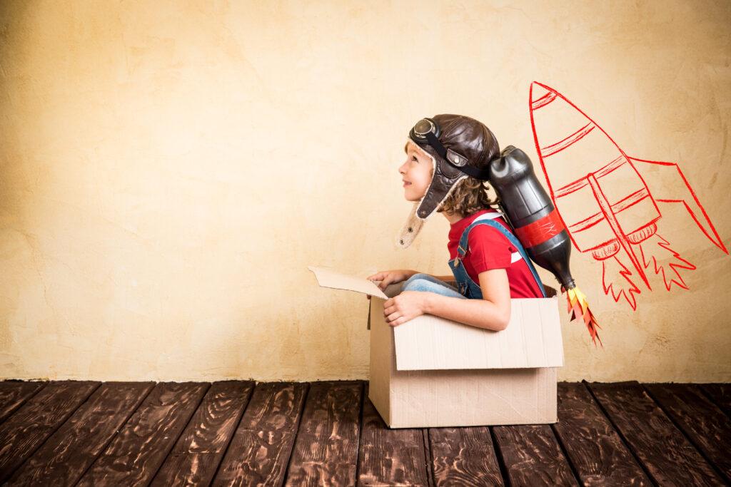 Dziecko siedzi w kartonie i udaje rakietę.